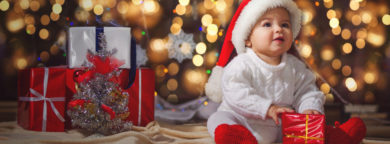 Little smiling boy (baby) in a white knitted sweater and hat of Santa Claus on a background of Christmas garland and gift boxes with ribbon.