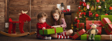 Merry Christmas and Happy Holidays! Two cheerful cute children girls with present. Kids hold a gift box near Christmas tree indoors.